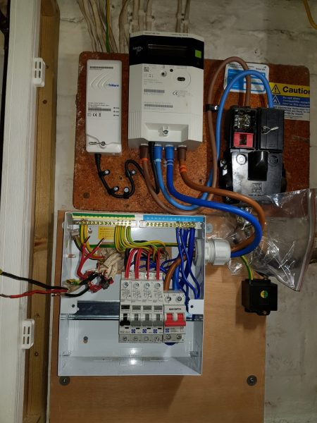 House B, Image 2. New fuse board during installation. Electrical cables feeding into the board no longer exposed.  Image shows the part of the wiring completed and part unfinished.