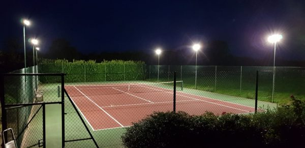 Mounted LED flood lights offer energy efficient illumination to a tennis court in Faversham, Kent